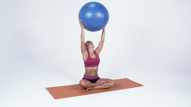 ws young woman lifting fitness ball / orem, utah, usa - orem video stock e b–roll