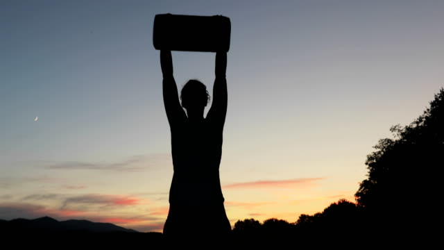 young woman lifting weight bag outdoors at twilight - flexing muscles stock videos & royalty-free footage