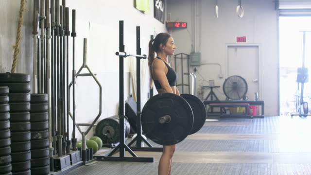 stockvideo's en b-roll-footage met ws young woman lifting weights in a gym - zwaar