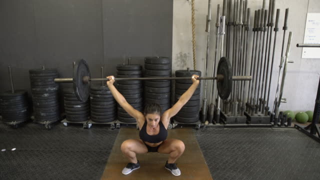 vídeos de stock, filmes e b-roll de ws young woman lifting weights in a gym - treino cruzado