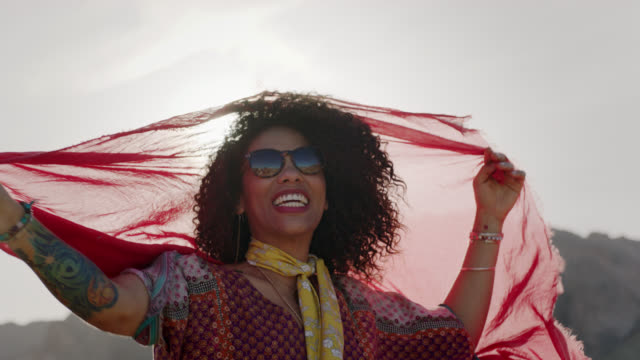 MED SLO MO. Young woman lifts shawl in the wind and holds it around her hair as she poses for camera in the desert sun.