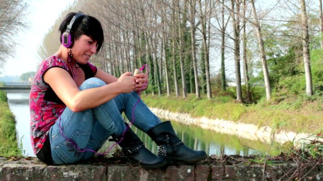 Young woman listen music using headphones