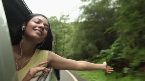 young woman listening music in a car, malshej ghat, maharashtra, india - exalterande bildbanksvideor och videomaterial från bakom kulisserna