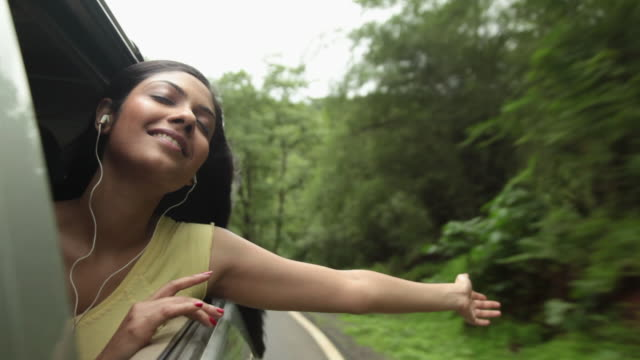 young woman listening music in a car, malshej ghat, maharashtra, india - kopfhörer stock-videos und b-roll-filmmaterial
