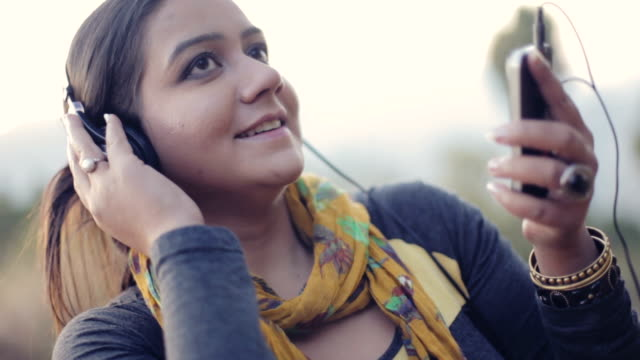 Young woman listening music in fresh air.
