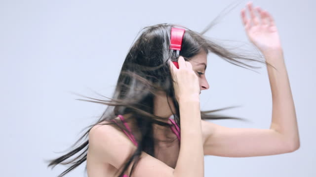 young woman listening music in headphone - nodding head to music stock videos and b-roll footage