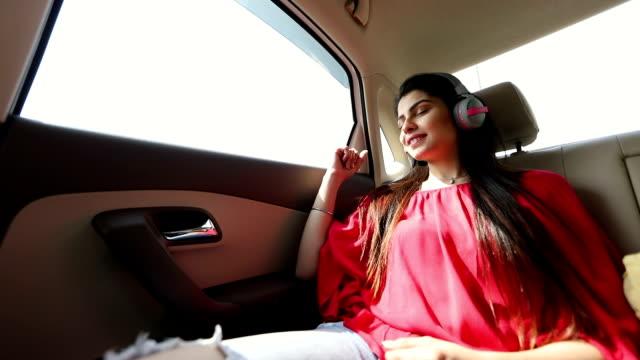 stockvideo's en b-roll-footage met young woman listening music in the car, delhi, india - passagiersstoel
