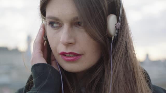 Junge Frau Musik hören auf Dach