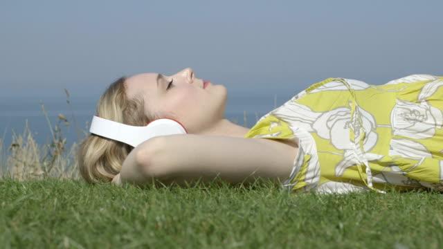 vídeos y material grabado en eventos de stock de joven mujer escuchando música - manos detrás de la cabeza