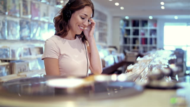 4K: Young woman listening records in store