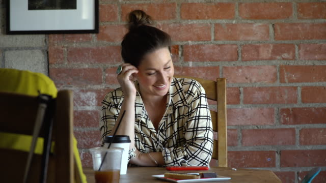 Young Woman Listening to a Podcast in a Cafe