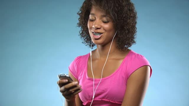 vídeos y material grabado en eventos de stock de young woman listening to mp3 player - vea otros clips de este rodaje 1164