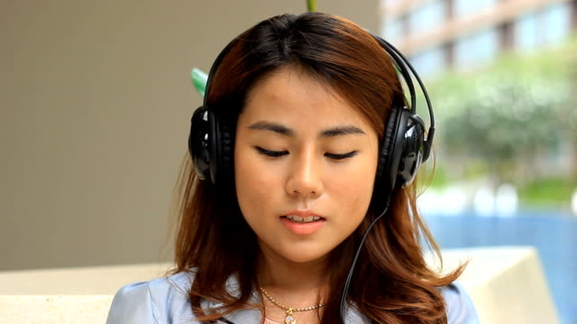 young woman listening to music and signing - bluetooth stock videos & royalty-free footage