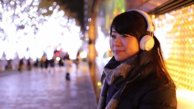 junge frau weihnachten nachts musik hören - japan stock-videos und b-roll-filmmaterial
