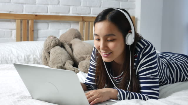Young woman listening to music by headphones with Laptop on the bed, Love music