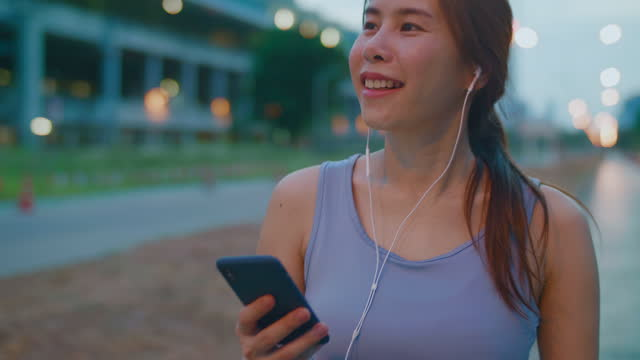 young woman listening to music during a workout in the city - only young women stock videos & royalty-free footage