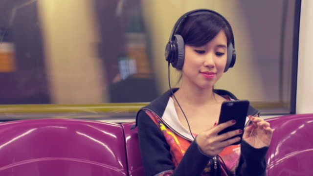 vídeos de stock e filmes b-roll de ms young woman listening to music on a train - ásia