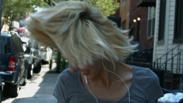 a young woman listening to music on headphones and rocking out outside in new york city - head banging stock videos & royalty-free footage
