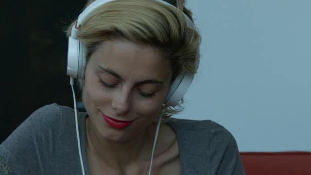 vídeos de stock, filmes e b-roll de a young woman listening to music on headphones inside - cabelo de comprimento médio