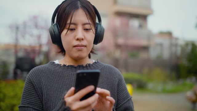 vídeos y material grabado en eventos de stock de joven escuchando música mientras usa teléfono inteligente en parque público - waist up