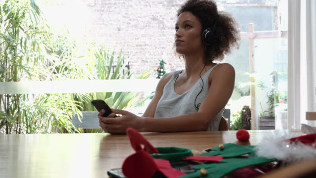 A young woman listening to music with Christmas decoration around her