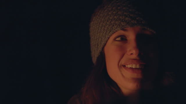 CU. Young woman listens to friends talk around campfire at night.