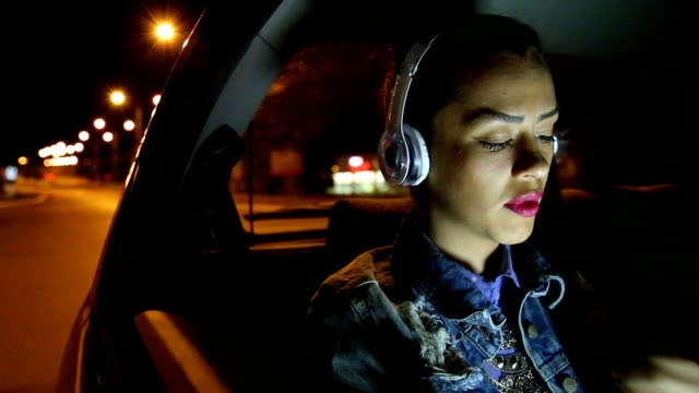 young woman listens to music in the car