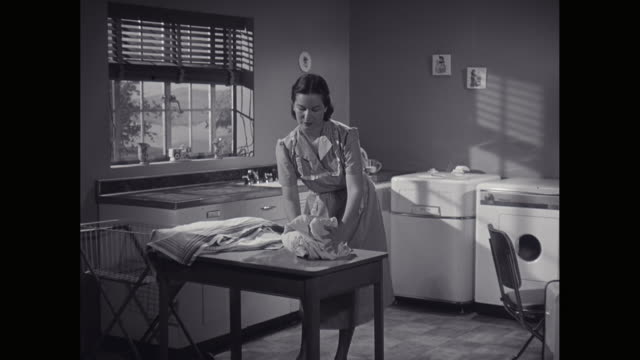 ms young woman loading laundry into washing machine / united states - 1940 stock-videos und b-roll-filmmaterial