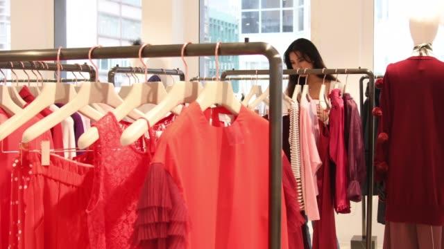 vídeos y material grabado en eventos de stock de mujer joven buscando una ropa carriles mientras compras en boutique - vestimenta para mujer