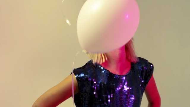 young woman looking at balloons floating up, slow motion - bangs stock videos & royalty-free footage