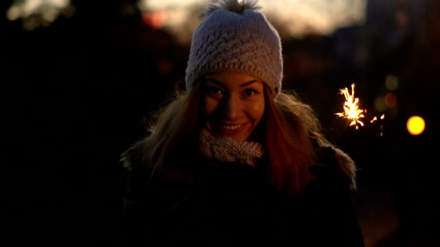 vídeos de stock e filmes b-roll de young woman looking at camera and holding sparklers in hand. - gorro de lã