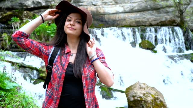 Junge Frau, Blick in die Kamera, während bei den Wasserfällen