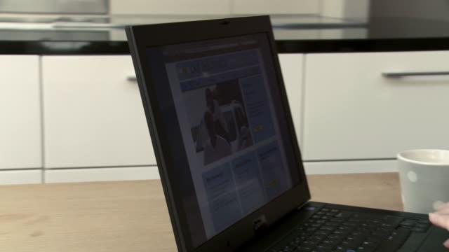 vidéos et rushes de young woman looking at car insurance on laptop, using the phone - téléphone sans fil
