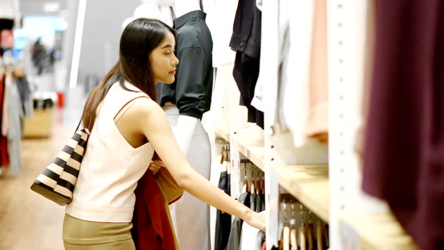 young woman looking at clothes in fashion store - top garment stock videos & royalty-free footage