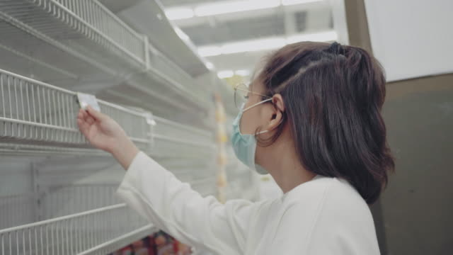 young woman looking at empty shelves at a grocery store in bangkok, thailand. - retail display stock videos & royalty-free footage