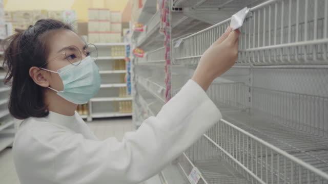 stockvideo's en b-roll-footage met jonge vrouw die lege planken bij een kruidenierswinkelopslag in bangkok, thailand bekijkt. - winkeldisplay