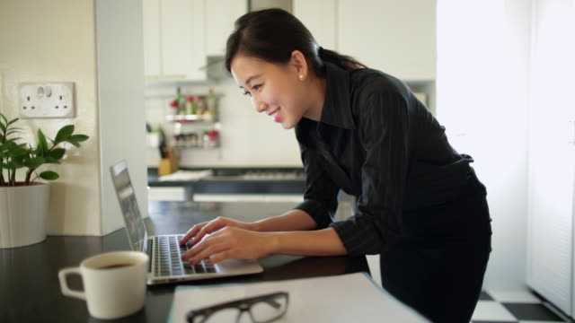 cu young woman looking at laptop computer in kitchen - 在宅勤務点の映像素材/bロール
