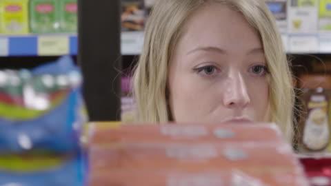 ds ung kvinna som tittar på produkter i en livsmedelsbutik - etikett bildbanksvideor och videomaterial från bakom kulisserna