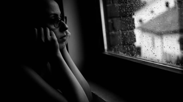 young woman looking at rain through the window - nostalgia video stock e b–roll