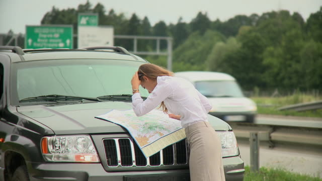 ms young woman looking at road map next to highway, ljubljana, slovenia - road map stock videos & royalty-free footage