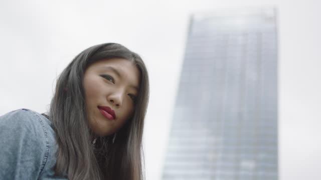 vídeos y material grabado en eventos de stock de mujer joven mirando rascacielos - comunidad global