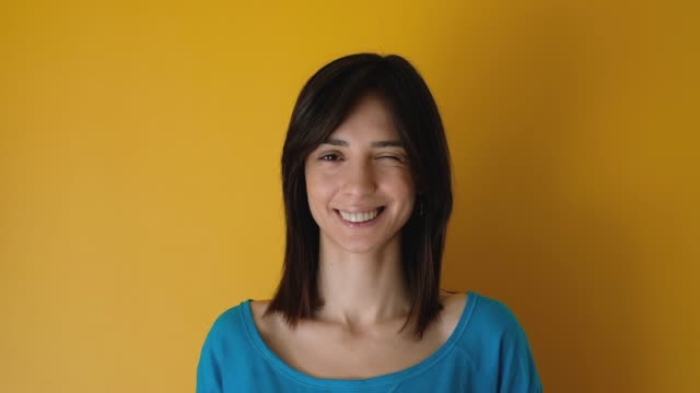 young woman looking at the camera smiling and winking on yellow background - mouth open stock videos & royalty-free footage
