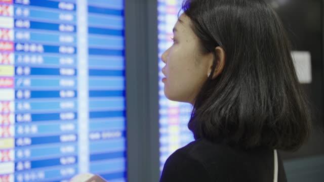 ung kvinna som tittar på flyginformations visningen på airport. - digital skyltning bildbanksvideor och videomaterial från bakom kulisserna