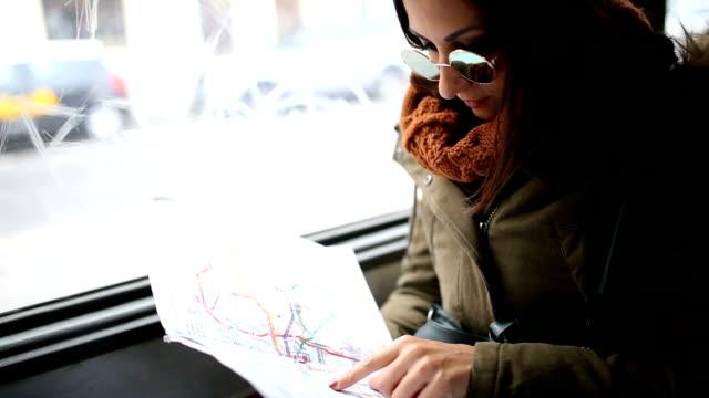 Ung kvinna tittar på kartan i en transport