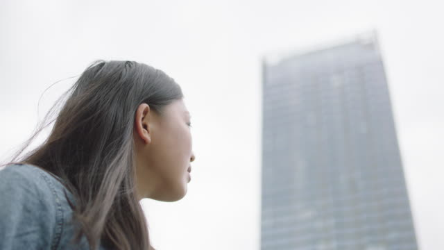 young woman looking at the skyscraper - upgrade stock videos and b-roll footage