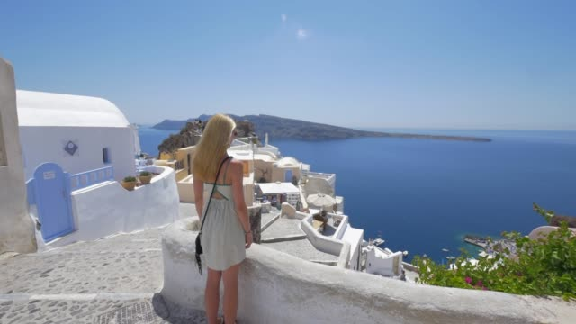 a young woman looking at the view, traveling in santorini, greece, europe. - slow motion - santorini stock videos & royalty-free footage
