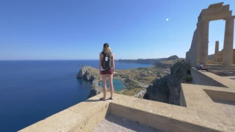 a young woman looking at the view with ancient ruins, traveling in lindos, greece, europe. - santorini stock videos & royalty-free footage