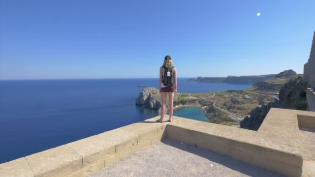 a young woman looking at the view with ancient ruins, traveling in lindos, greece, europe. - slow motion - insel rhodos inselgruppe dodekanes stock-videos und b-roll-filmmaterial