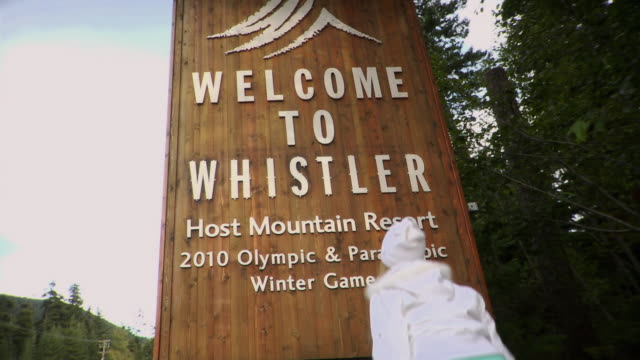 ms young woman looking at welcome to whistler sign and jumping  / whistler, british columbia, canada - winter olympic games stock videos and b-roll footage