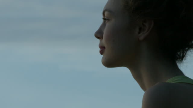 a young woman looking confidently towards the sky outside in new york city in slow motion - profile stock-videos und b-roll-filmmaterial